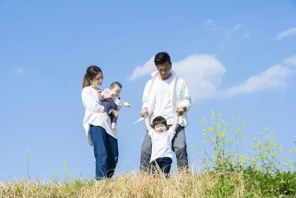 青空のもと、笑顔で歩く親子4人