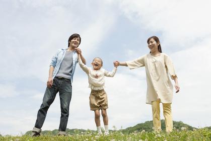笑顔で手をつなぐ家族3人