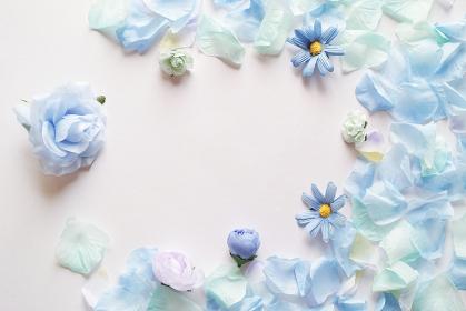 白背景に造花の青い花と花びらで囲んだフレーム。平置きの俯瞰撮影。