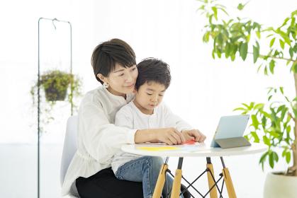 タブレットPCを見ながら折り紙をする親子