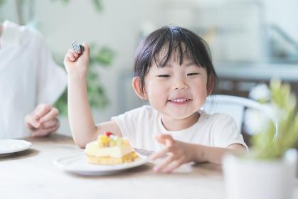 部屋のテーブルでケーキを食べる親子