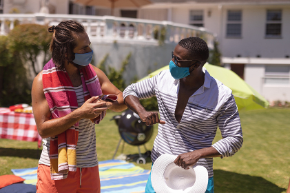 Two diverse male friends wearing face masks bumping elbows at a pool party. Health and hygiene precautions while hanging out and relaxing outdoors in summer during coronavirus covid 19 pandemic.