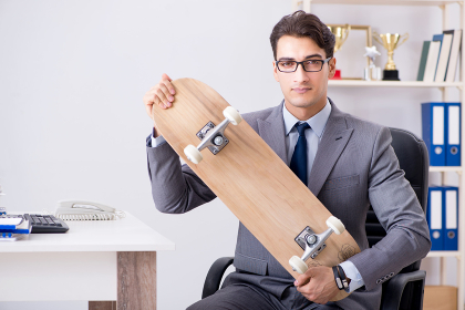 Young businessman riding skate in office during break