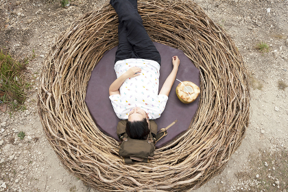 Young Woman Taking A Break And Drinking A Coconut Inside A Nest In Front Of The Sea, Bali, Indonesia