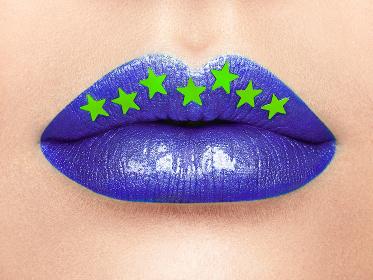 Close up view of Beautiful Woman Lips with Purple Lipstick.  Cosmetology, drugstore or Fashion Makeup Concept Gold stars. Beauty studio shot. Passionate Kiss