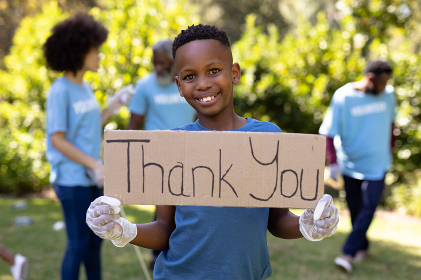 Mixed race boy spending time outside with his family, holding a thank you sign, looking at the camera and smiling, with his family in the background, all wearing blue volunteer t shirts, on a sunny day