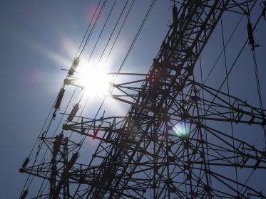 高圧送電線の鉄塔と逆光の太陽