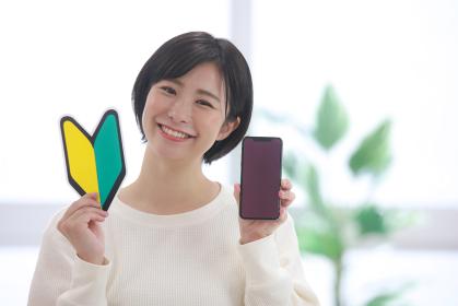 スマートフォンと初心者マークを持つ女性社員