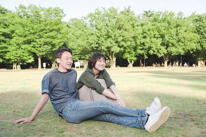 芝生に座る若いカップル(リラックス・公園)
