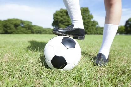 サッカーボールに足を乗せる女子中学生