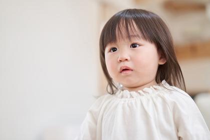 不安な表情でママを追いかけるアジア人の幼児