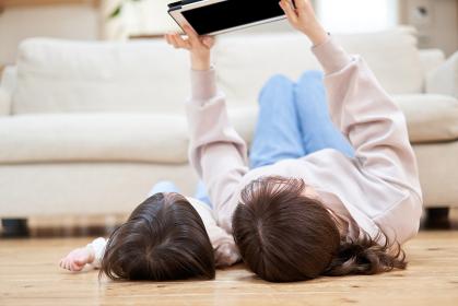 床暖房のフローリングに寝っ転がってタブレットを見るアジア人の親子
