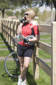 Cyclist with her bike leaning on fence while using cell phone