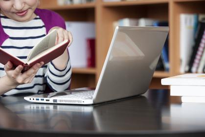 図書室でPCに向かって勉強する日本人女性