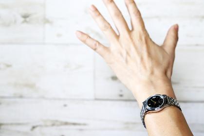 手でパーサインをするシルバーの腕時計をした女性の手元
