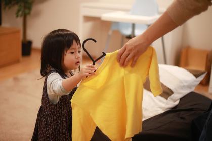 洗濯物を干す手伝いをする女の子