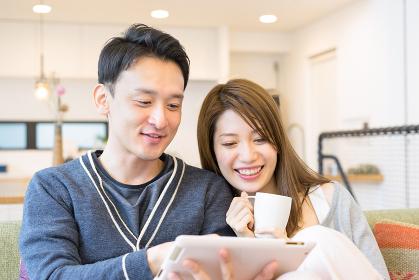 タブレットPCを見る笑顔の幸せなカップル