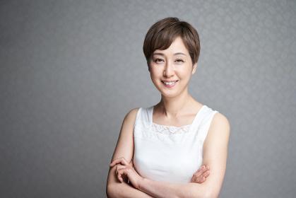 カメラ目線で腕組みをする中年の日本人女性