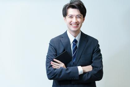 腕を組むポーズをする若手ビジネスマン
