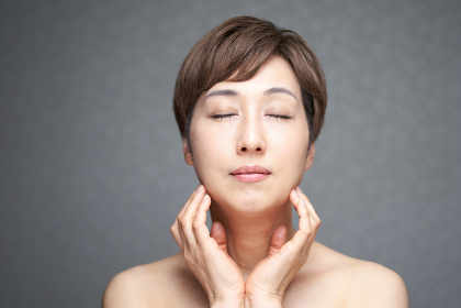 目をつぶって顎に手を当てる中年の日本人女性