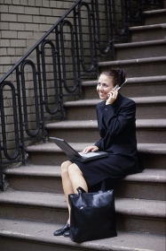 階段に座り電話をする女性会社員