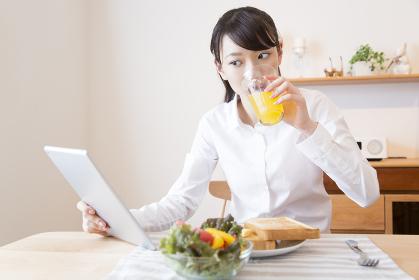 朝食を食べながらタブレットPCを見る女性