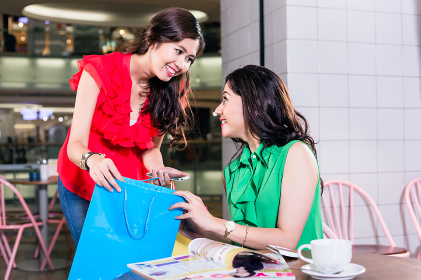 Cheerful woman showing to her best friend her purchase