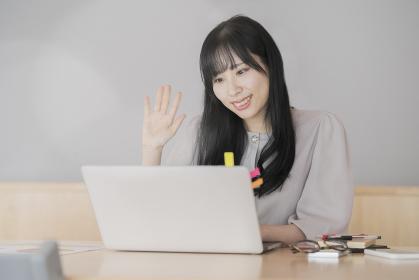 パソコンの画面に向かって、手を振る女性