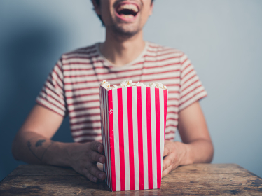 A happy laughing young man is sitting at a table with a box of popcorn