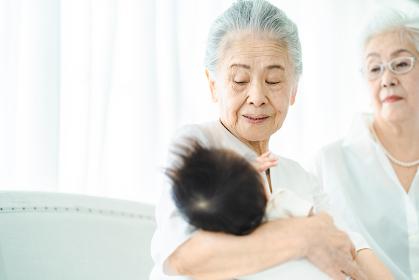 赤ちゃんを抱っこするシニア女性たち
