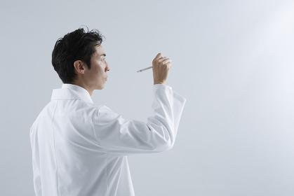 ペンを持つ白衣の男性 スタジオ撮影