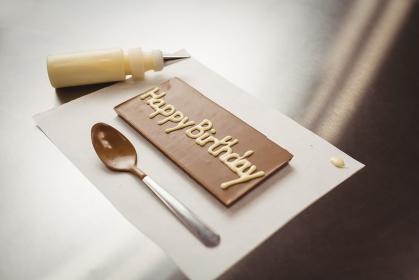 Happy birthday written on chocolate plaque