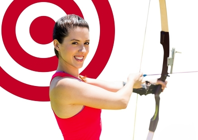 Portrait of woman aiming with bow and arrow at target