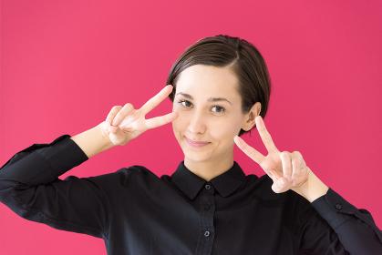 ピースマークをする若い女性(赤背景)