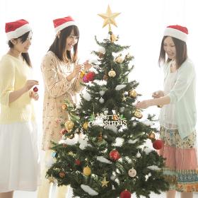 クリスマスツリーの飾り付けをする3人の女性