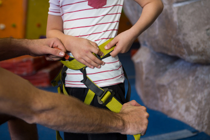 Trainer assisting boy to wear safety harness