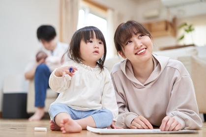 絵を描く母子と赤ちゃんの面倒を見るアジア人のお父さん