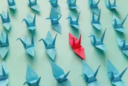 複数の左向きの青い折り鶴の中に一つだけ赤い折り鶴がある。