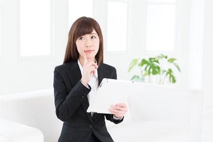 タブレットコンピューターを見る女性 ビジネス 考える