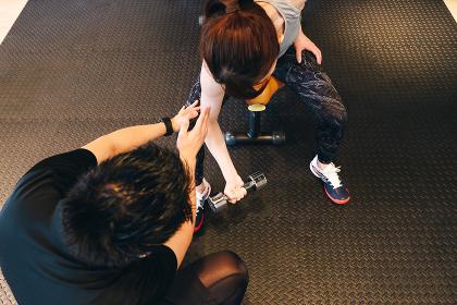 ダンベルを持ち上腕二頭筋を鍛える女性