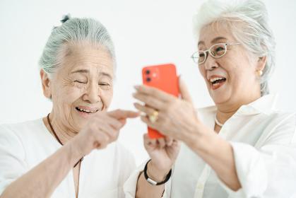 笑顔でスマートフォンの画面を見るシニア女性たち