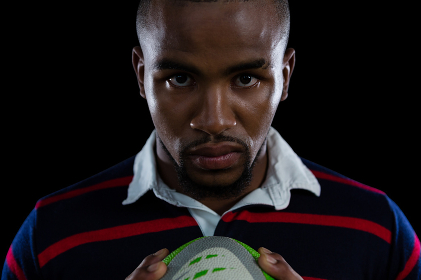 Close up portrait of sportsman holding rugby ball