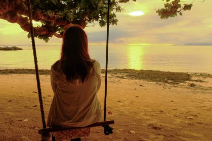 海辺のブランコに座る女性
