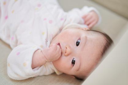 指をくわえるアジア人の女の子の赤ちゃん