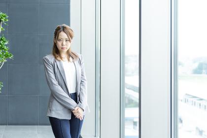 窓際に立つ社会人の女性(ビジネスイメージ)