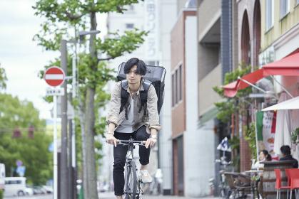 自転車で配達をする若い日本人男性