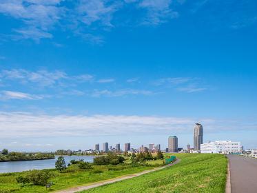 青空の荒川の堤防と川口市の高層ビル