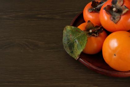 木製の平皿に盛られた柿 1