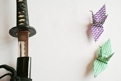 白い紙の上に置いた抜きかけの黒い日本刀と緑色の鹿の子文の折り鶴に紫色の矢絣の折り鶴