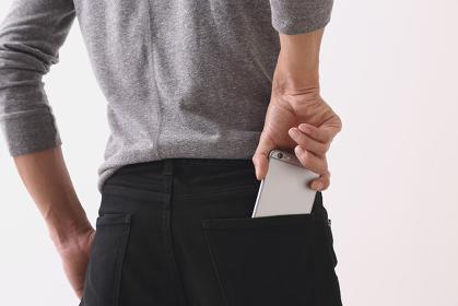 iPhoneを後ろポケットにいれる男性